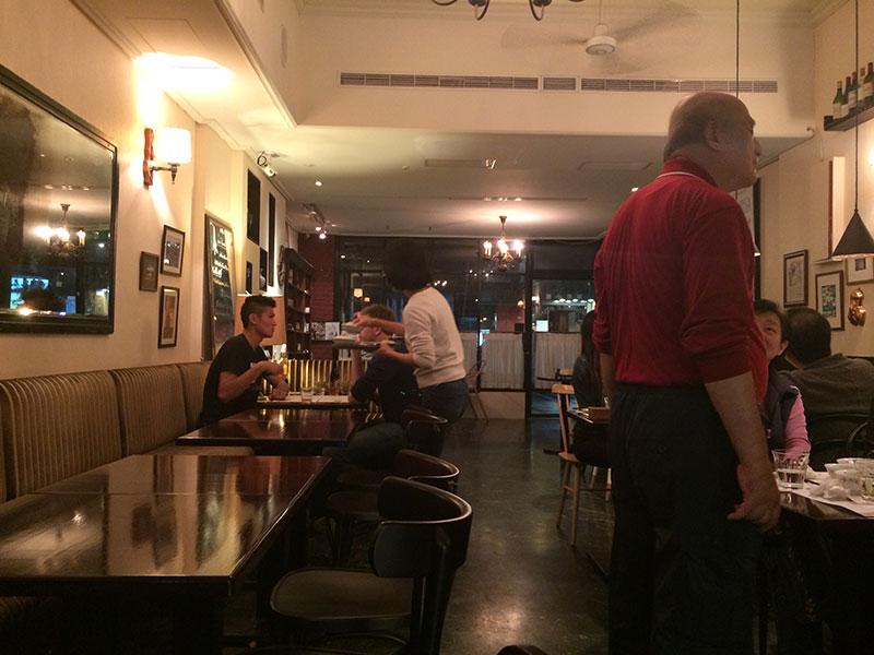 赤いポロシャツを着たシェフ。和やかになじみのお客さんとお話しています。